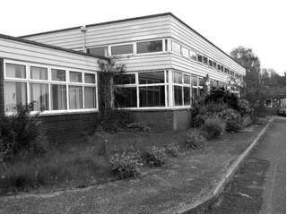 Newcombes Resources Centre standing empty and covered in weeds.